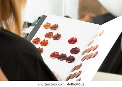 Hairdresser salon visitor looking at the book of color samples close up. Visitor sitting at hair stylist office choosing new hair color. Haircare, beautician, dyeing or changing hair colour concept