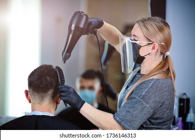 A hairdresser with security measures for Covid-19, blow-dry a man in a medicine mask, social distance, cutting hair with a medical mask, eye mask and rubber gloves in a beauty salon
