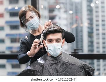 Friseur mit Sicherheitsmaßnahmen für Covid-19 oder Coronavirus, Haare schneiden einen Mann in einer medizinischen Maske, soziale Distanz, schneiden Haare mit einer medizinischen Maske, Augenmaske in einem Schönheitssalon, neue normal 2020