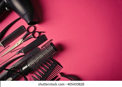 Hairdresser set with various accessories on pink background