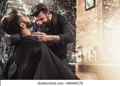 Hairdresser shaving  beard with a hair-clipper