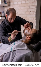 Hairdresser shaving his beard with a razor to a client