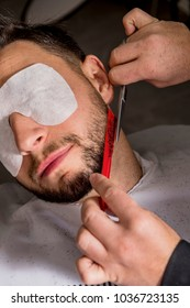 Hairdresser shaving his beard with scissors to a client