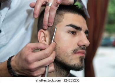 Hairdresser Shaving Man's Chin With A Straight Razor - Handsome Young Hairdresser Giving A New Haircut To Male Customer At Parlor
