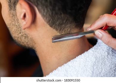 Hairdresser shaving man's neck with a straight razor