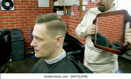the hairdresser shows the client a hairdo in the mirror 4k
