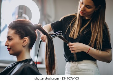 Hairdresser straightens the hair girl with an iron in the beauty salon