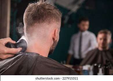 hairdresser  sweeps odds and ends  with brush  off  back of the head  of handsome satisfied  client in  professional  hairdressing salon