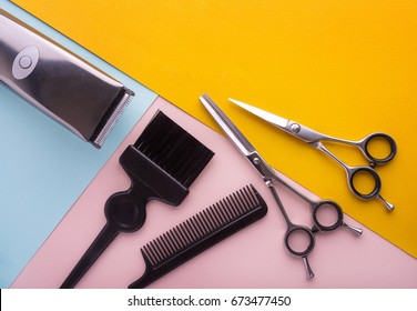 Hairdresser tools on color background with copy space at top.