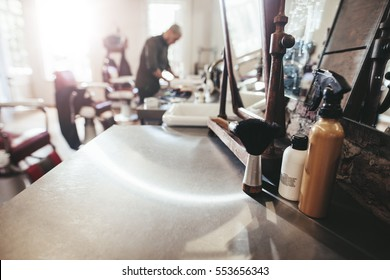 Hairdresser tools on counter with barber in background. Barber shop with hairstyling equipments,