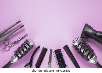 Hairdresser tools on lilac pink background with copy space in center, top view, flat lay. Comb, scissors, thinning scissors, hair clip, hairdryer, curling iron
