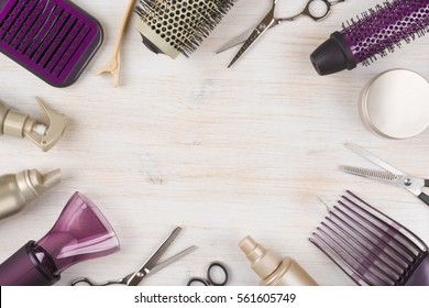 Hairdresser tools on wooden background with copy space in center.