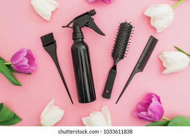Hairdresser tools - spray, combs and tulips flowers on pink background. Beauty concept. Flat lay, top view