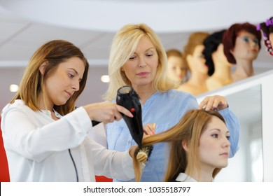 hairdresser and trainee putting hair-curlers