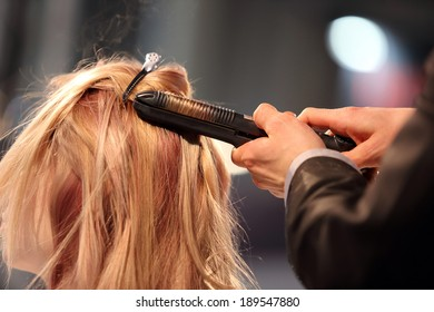Hairdresser turns hair curling iron of young girl