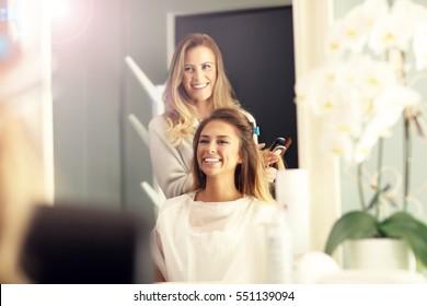 Hairdresser using hair straightener in studio