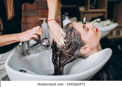 Hairdresser washing hair of happy young woman, girl and do relaxing massage at beauty saloon