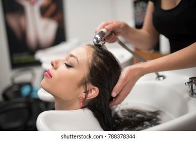 Hairdresser washing latin woman hair in hairdressing saloon sink