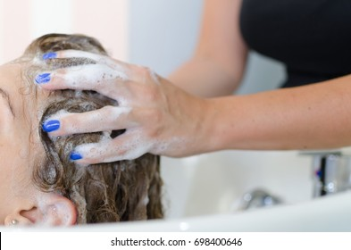Hairdresser washing woman hair and do head massage for better circulation in beauty and healthy salon.