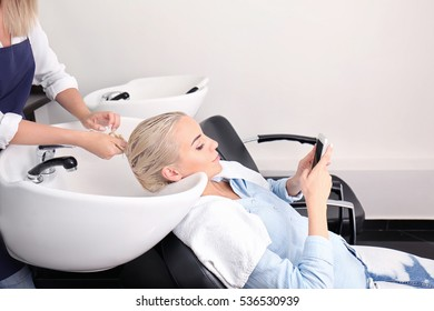Hairdresser washing woman's hair in salon