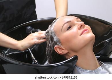 Hairdresser washing woman's hair in hairdresser salon