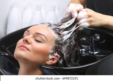 Hairdresser washing woman's hair in hairdresser salon