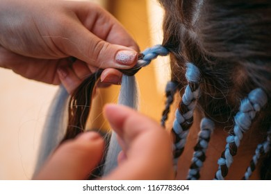 Hairdresser weaves braids with kanekalon material to young girl head, making creative hairstyle with thick plaits or pigtails also known as African or Afro braids, close up