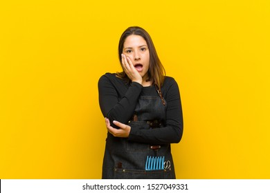 hairdresser woman open-mouthed in shock and disbelief, with hand on cheek and arm crossed, feeling stupefied and amazed against orange background