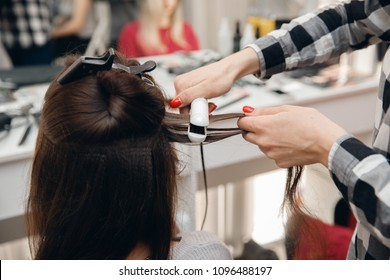 Hairdresser woman straightens her hair and makes styling, close-up of curling iron in salon