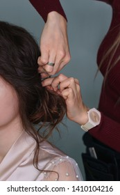 Hairdresser at work in process of creating wedding hairstyle. Master fixes lower topknot of hair with invisible hairpins and hat pins. Beauty is in details. Perfect in little things. Beauty industry