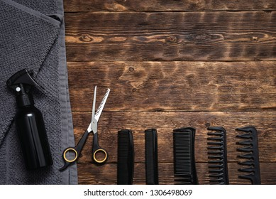 Hairdresser work table background with copy space. A various hairdressing tools such a hairbrushes, sprayer, towel and a scissors on a wooden board.
