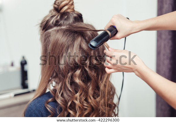 Hairdresser working with beautiful woman brown hair in hairdressing salon. Close up view of hand, curling iron and the appliance