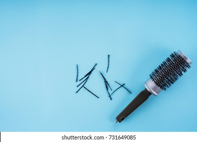 hairdresser's concept: hairbrush, plaice, hairpins on a blue background