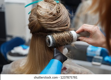 Hairdressers hands drying blond hair with blow dryer and round brush