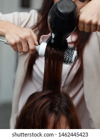 Hairdressers hands drying brunette hair with blow dryer and round brush