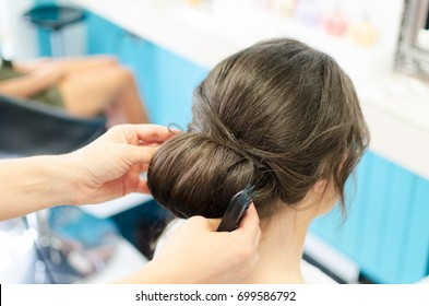 Hairdressers hands make a beautiful hair bun or twisted hair for woman weeding. Happy client in hair beauty salon.