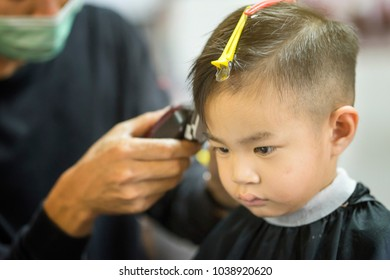 Hairdresser's hands making hairstyle to child.