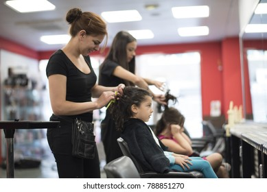 Hairdressers with little girls in beauty center saloon