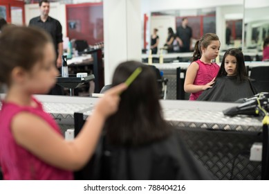 Hairdressers with little girls. One girl combing other in hair school