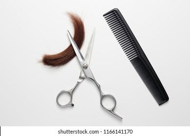 Hairdresser's scissors, comb and with lock of hair, on white background.