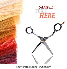 hairdressers scissors and dyed locks of hair on white