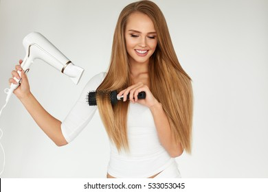 Hairdressing. Beautiful Woman Drying Healthy Long Straight Hair Using Blowing Dryer. Attractive Smiling Girl With Blonde Hair Using Hairdryer And Round Dry Brush. Hair Care Concept. High Resolution
