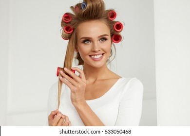 Hairdressing. Happy Woman Applying Hair Rollers On Beautiful Healthy Blonde Hair. Attractive Smiling Girl With Hair Curlers On Head Curling Hair For Perfect Curls. Hairstyle. Beauty. High Resolution