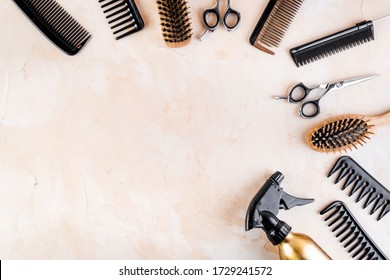 Hairdressing instruments. Combs, scissors and spray on beige desk from above frame space for text