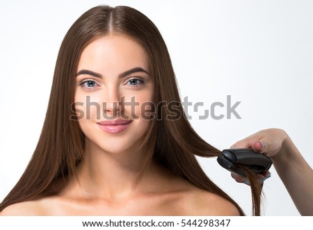 Hairdressing process. Girl model Hair Straightening Irons.Beautiful Woman with Long Straight Hair. Healthy Hair. Hairstyling.
