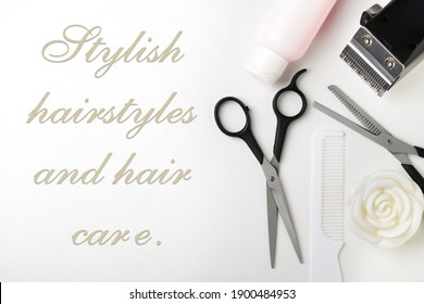 Hairdressing supplies - scissors, comb, hair lotion, trimmer, on a white background. Copy space. Shallow depth of field.