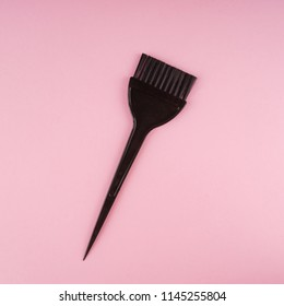 Hairdressing tools with copy space, hair coloring brush on pastel colored paper background, top view and flat lay.