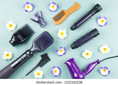 Hairdressing tools with flowers on blue wooden background