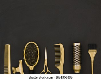 Hairdressing tools in gold on a dark gray background with space for text on top. Hairdressing accessories, scissors, hairpins and combs.
