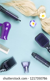 Hairdressing tools and hair extensions on blue wooden background. Top view